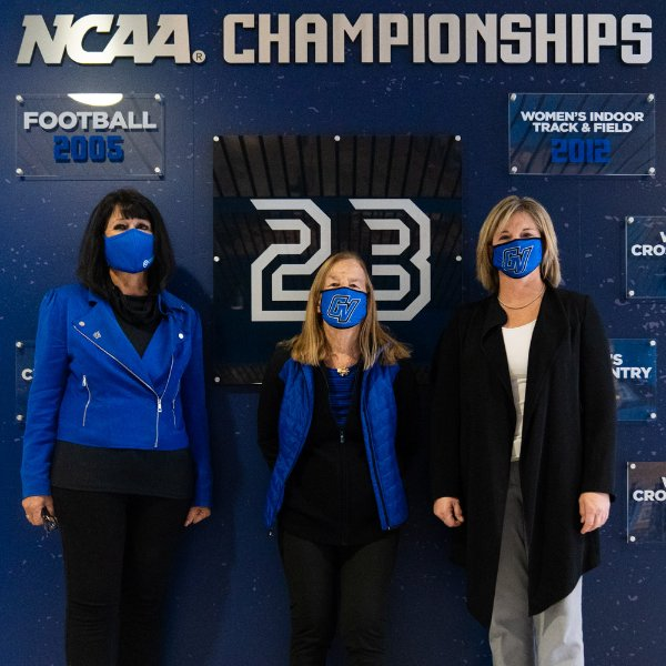 from left President Mantella, Joan Boand and Keri Becker standing in front of display wall
