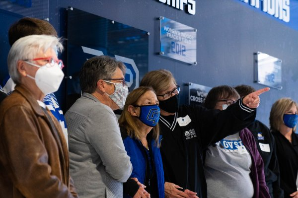 attendees all in masks stand with Joan Boand at wall
