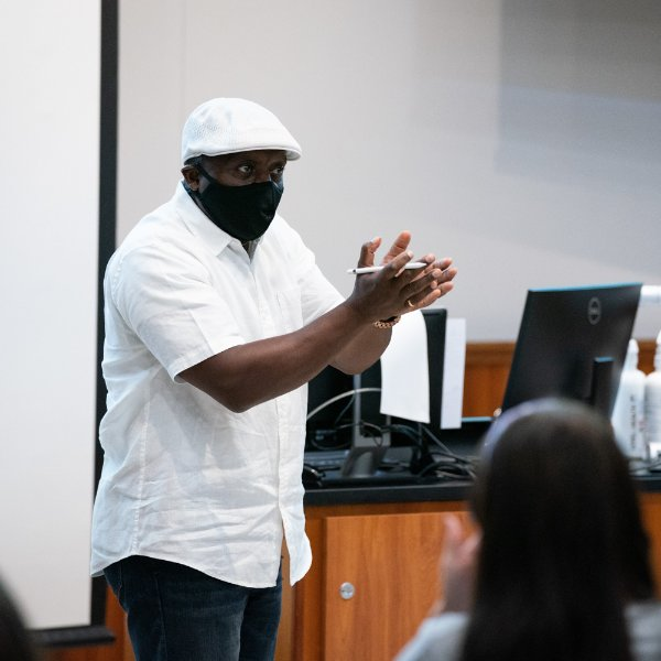 Felix Ngassa teaching in front of students in mask.