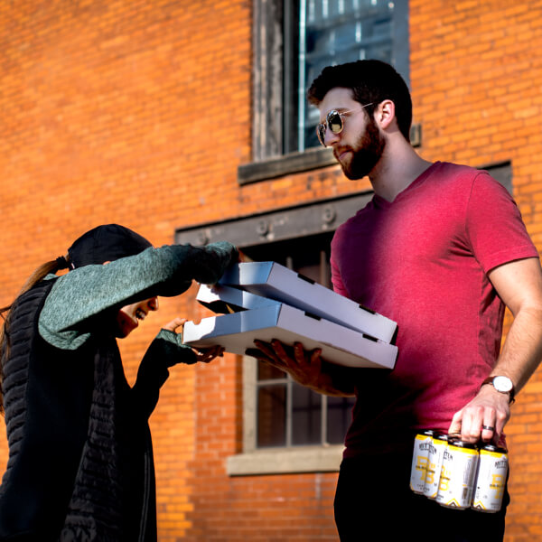 "Grand Valley alum Nate Gillespie and his wife, Nichole, pick up pizza and beer from Mitten Brewing Company on April 2. The business was a ""targeted spend"" for the Coronavirus Civilian Corps, a group he is leading."
