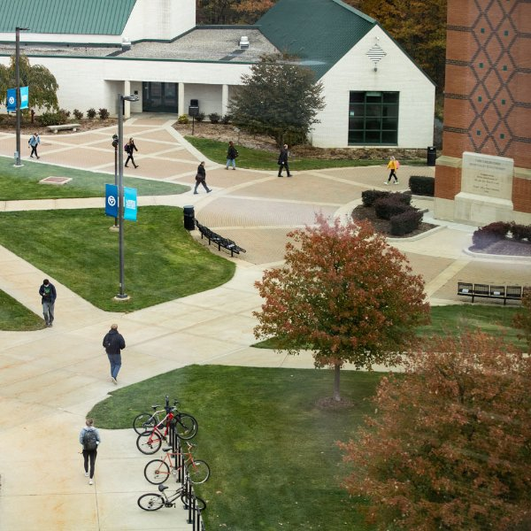 people walking on Allendale campus by carillon tower, lots of sidewalks pictured