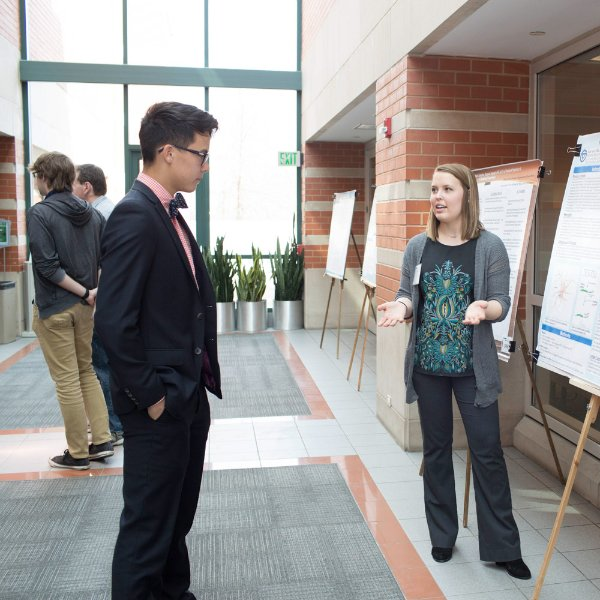 A Student Scholars Day participant stands next to a poster explaining it to another person.