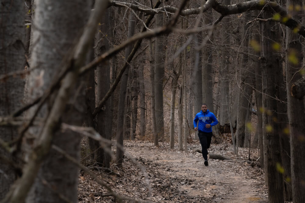 Jakyle Harris runs through the ravines on Grand Valley State University's campus on April 21, 2020.