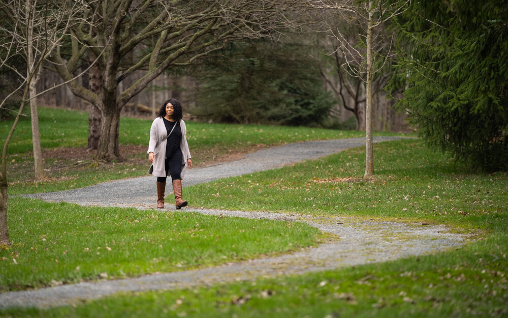 Senior Charity Foster walks through her favorite section of the trail that runs through the woods in the back of the GVSU Arboretum on April 23.
