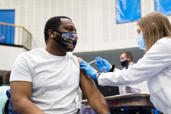 GVSU student Denzel Braswell gets the first dose of the Pfizer vaccine at the Fieldhouse.