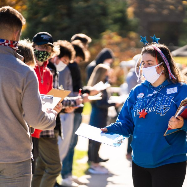 A student in a blue GVSU sweatshirt and holding clipboards hands a clipboard to a student waiting in a line to vote.