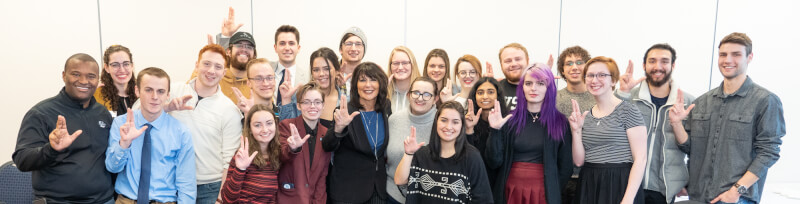 Philomena Mantella poses for a photo with a group of student senators. The group is smiling and holding up their index and middle fingers near their thumbs in the 'Laker Up' gesture.