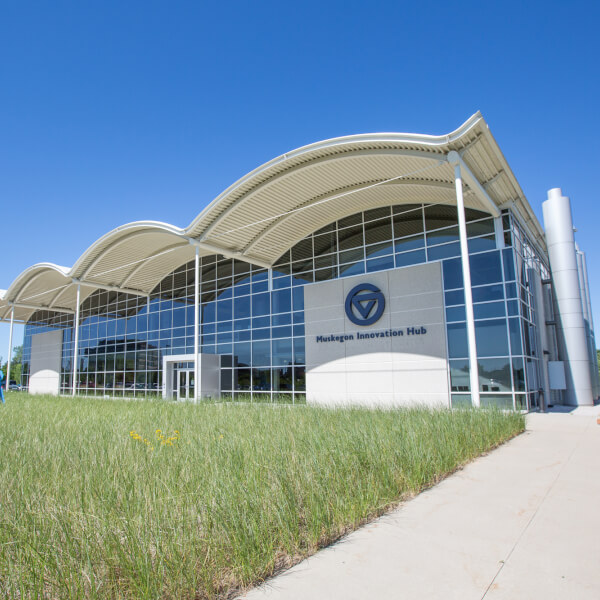 A photo shows the Muskegon Innovation Hub from the front, with large arching glass windows and a front landscape of dune grass.