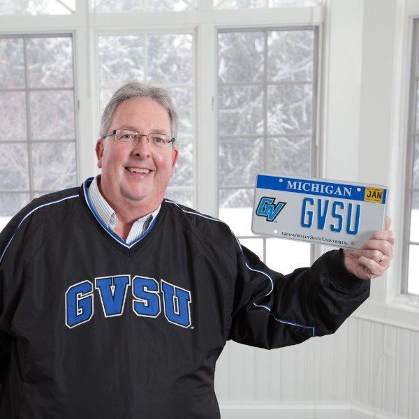 Bob Stoll holds a license plate with GVSU on it, a GVSU specialized plate