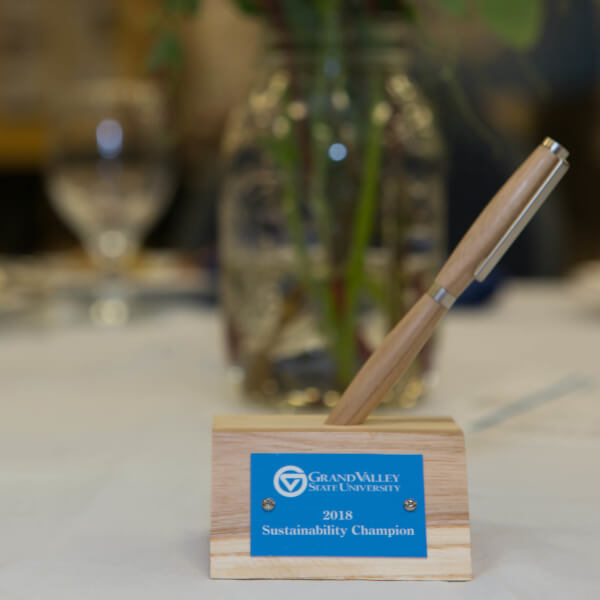A photo of a 2018 sustainability champion award made out of recycled wood from fallen ash trees on the Allendale Campus.