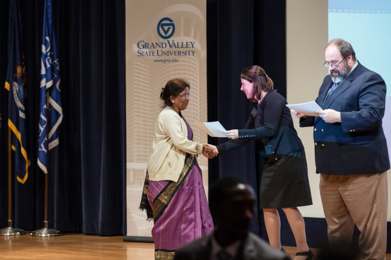 woman hands certificate to another woman on stage