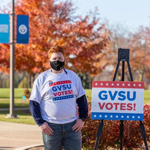 Sam Jacobs in mask standing outside next to GVSU Votes sign and wearing the same t-shirt, with GVSU Votes!
