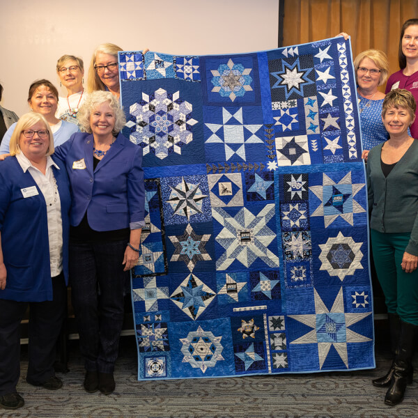 women standing in two rows surrounding a quilt