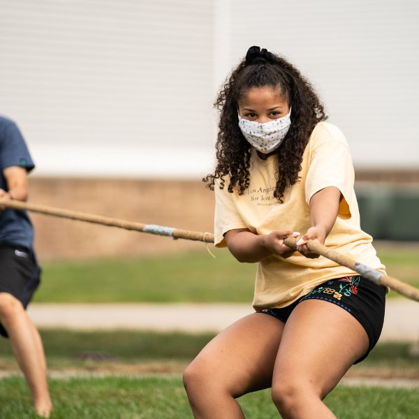 An international student wearing a mask participates in a game of tug of peace.