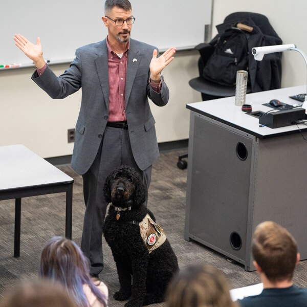 man at front of classroom, service dog at his feet