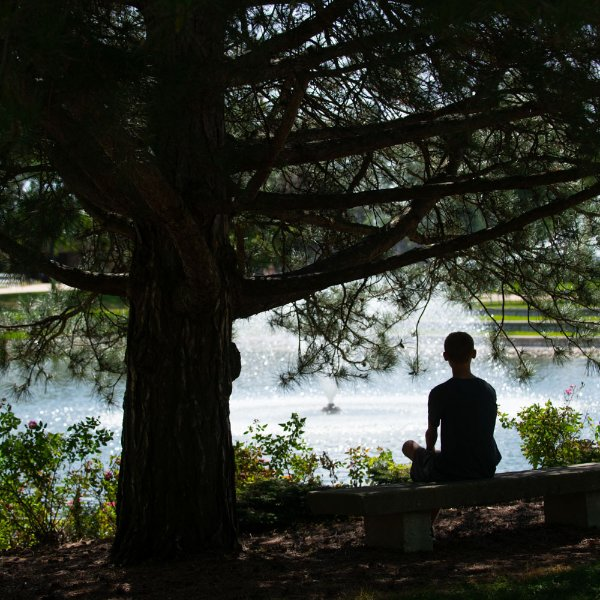 A G-V-S-U student sits by the Zumberge Pond on the Allendale Campus.