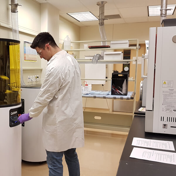 A technician in a lab coat stands in a lab in front of a Carbon, Inc., 3D printer. The printer is a tall cylinder with an amber plastic shield in front of it.