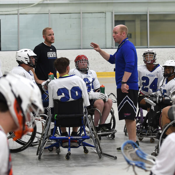coach standing in center of wheelchair lacrosse athletes