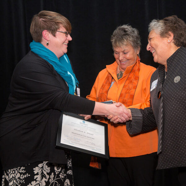 Three women on stage, one with certificate and shaking hands
