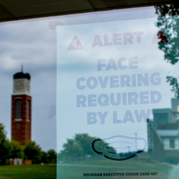 door sign that reads face coverings required by law