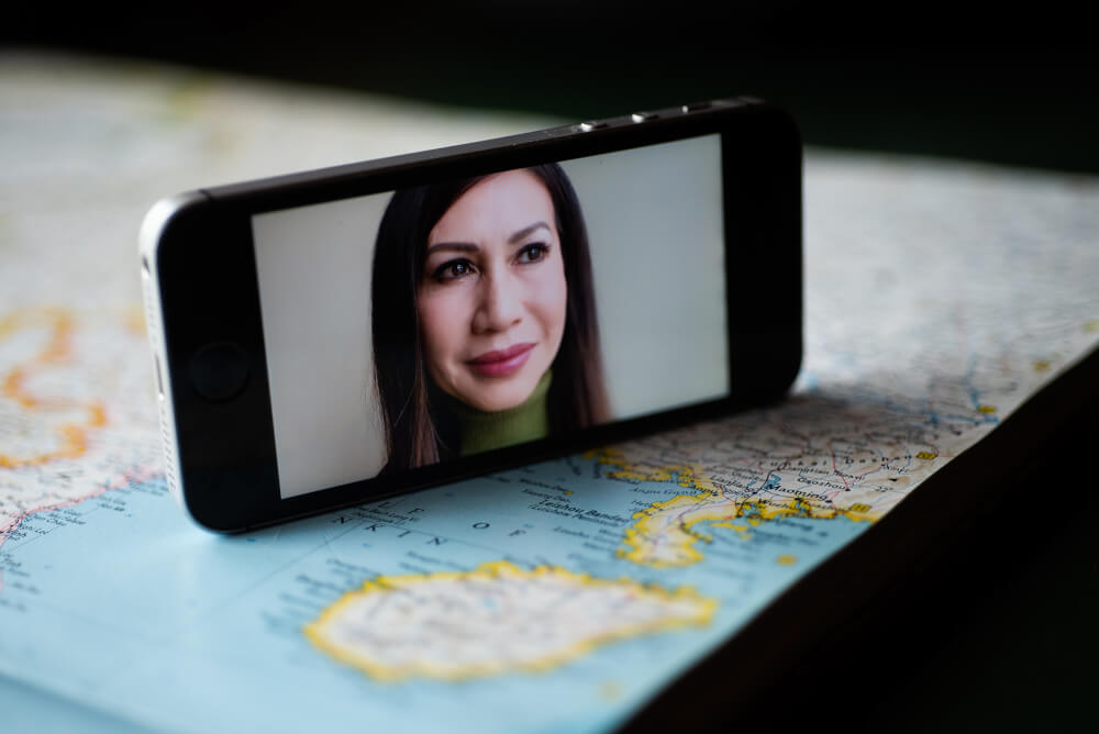 woman's face on cell phone, phone sitting on a map of China
