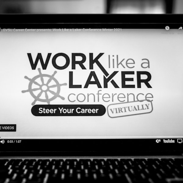 A black and white photo of a computer screen that shows text that reads work like a laker conference, steer your career virtually
