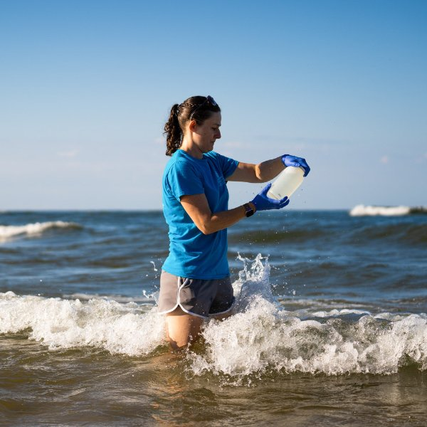 GVSU student Molly Lane collects samples for water quality testing from Lake Michigan at the Pere Marquette Beach