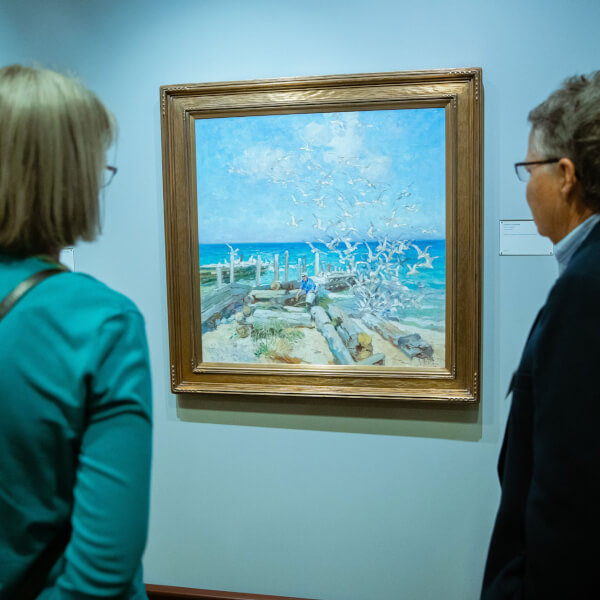 Visitors to the Gordon Gallery admiring one of the more than 150 works of art by Mathias Alten in Grand Valley's collection.