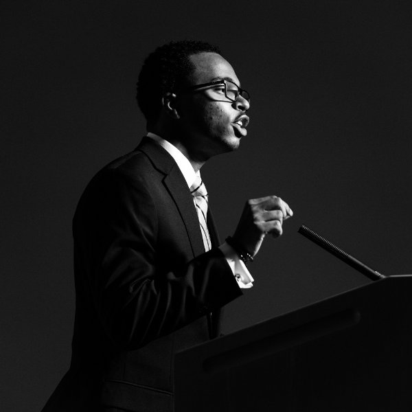 Julian Sanders gives remarks at a podium, in a black and white photo