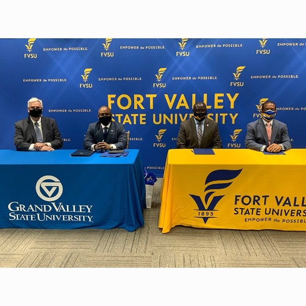 four people in masks seated at tables in front of sign at Fort Valley State University.