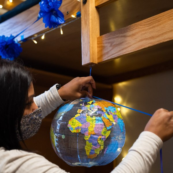 A GVSU employee hangs a globe in a campus residence hall.