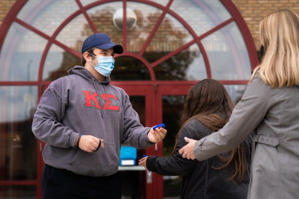 Vito Cannizzaro, a Grand Valley student, hands out wristbands to students who are using COVID-safe behavior.