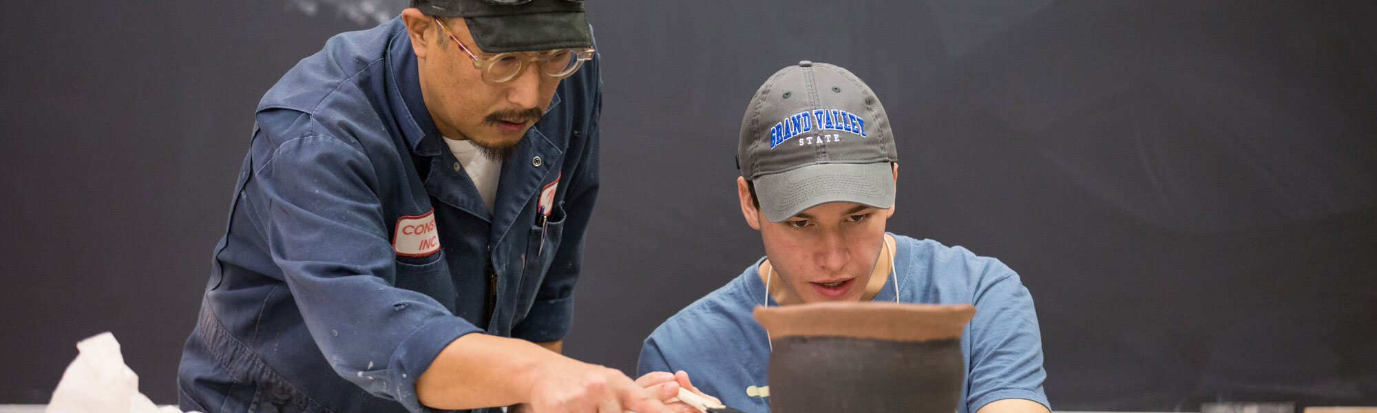 Photo of GVSU studio art student working with his professor in a sculpting class.