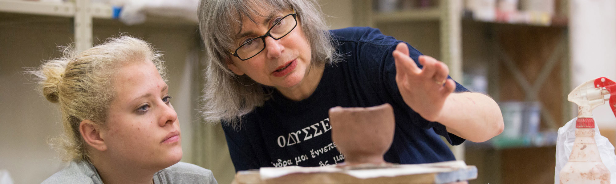 A GVSU student and faculty member working on pottery.