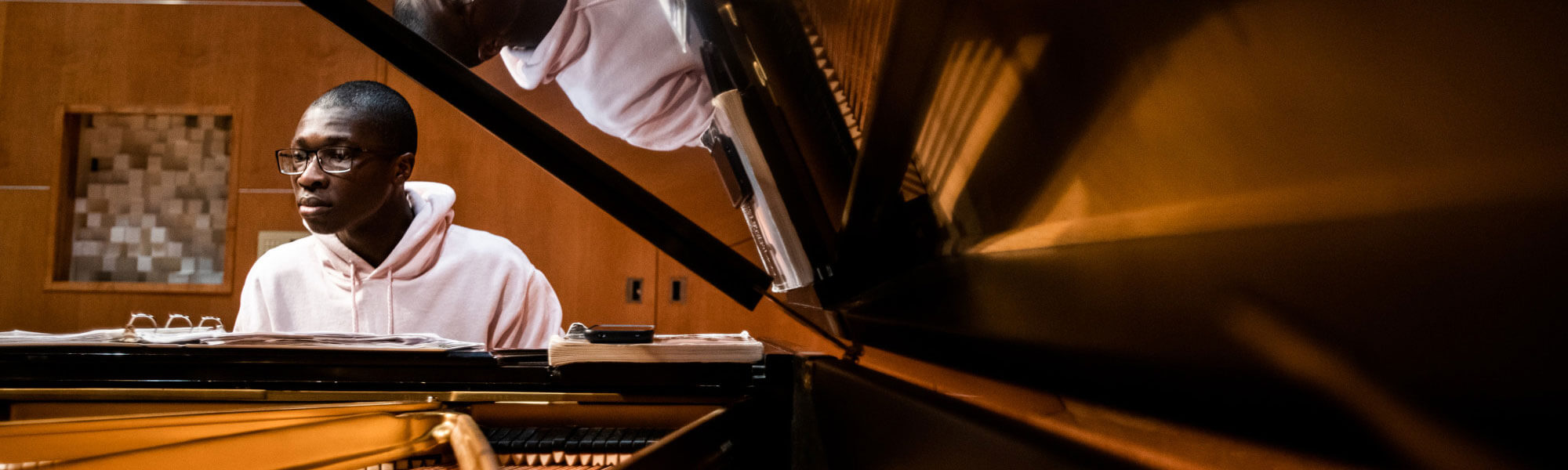 A GVSU music student plays the piano in the Louis Armstrong Theatre.